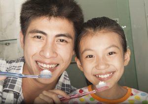dad and daughter brushing teeth