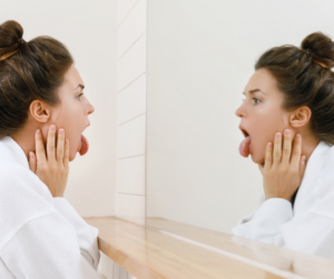 woman looking at her tongue in the mirror